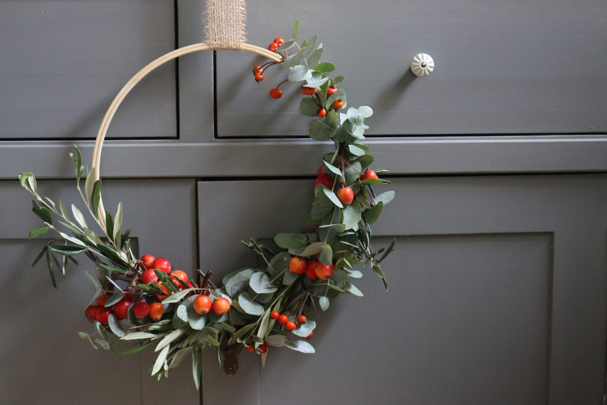 Krans met eucalyptus, olijftakjes, sierappeltjes en rozenbottels.